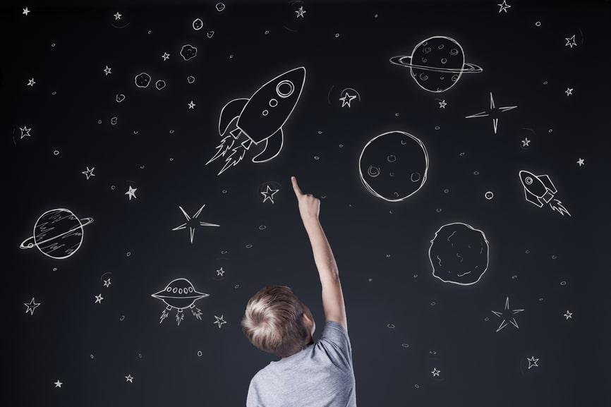 Little boy pointing at drawing sky at night